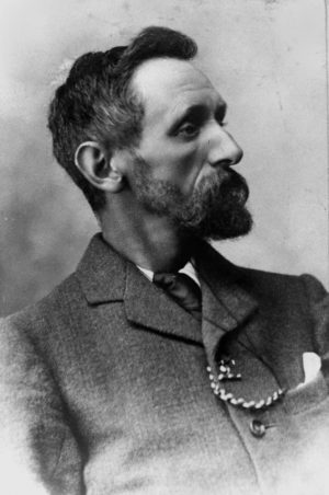 A black-and-white portrait of a bearded man with a suit