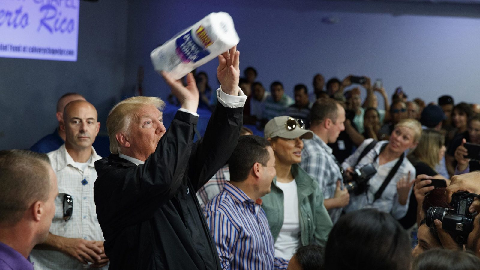 Trump throws a roll of paper towels into the crowd.
